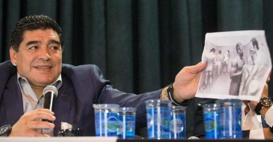 04.set.2013 - Ex-jogador argentino Diego Maradona recebe uma foto antiga das mãos de repórter do CQC durante encontro promovido pelo ex-presidente do Corinthians Andrés Sanchez em São Paulo