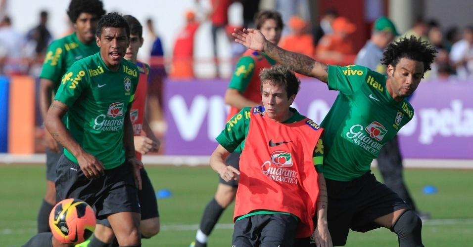 05.set.2013 - Bernard é cercado por Marcelo e Paulinho durante treino da seleção brasileira
