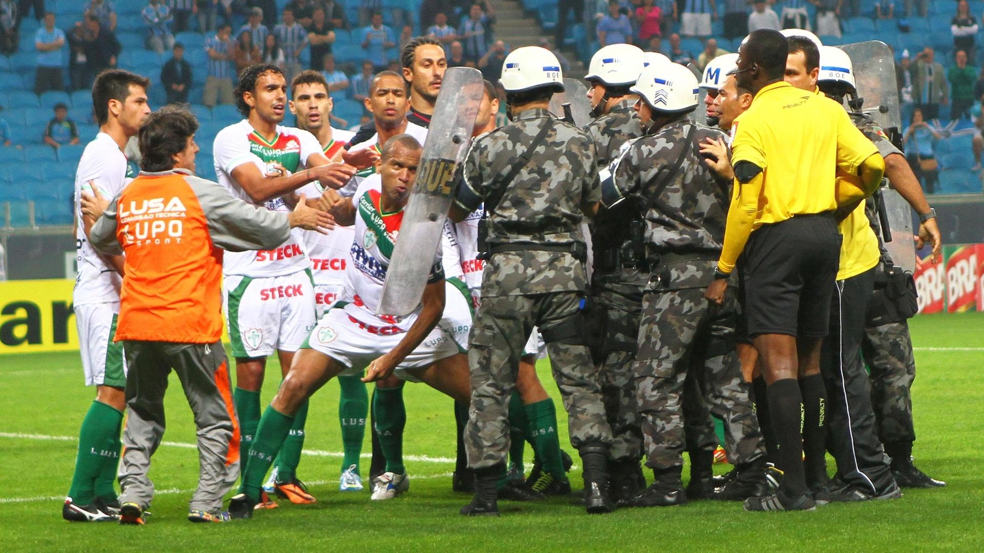 Zagueiro Valdomiro se prepara para acertar um soco no escudo de um policial militar após o jogo da Portuguesa contra o Grêmio, na Arena. Jogadores reclamavam de um pênalti marcado para os gaúchos (07/09/2013)