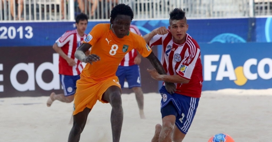 19.set.2013 - O marfinense Moustapha Sakanoko  disputa bola com Juan Lopez, do Paraguai, em partidas no Mundial de futebol de areia