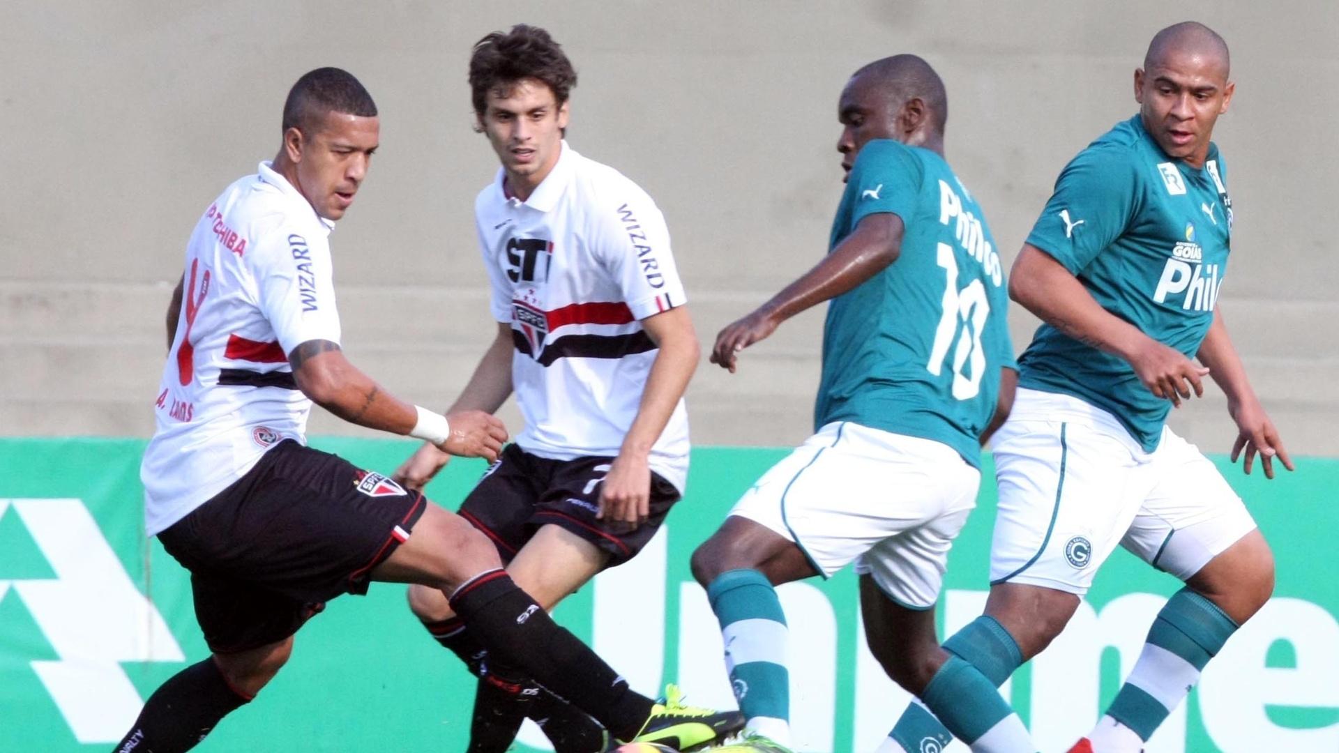 22.set.2013 - Observados por Rodrigo Caio e Walter, zagueiro Antonio Carlos, do São Paulo, disputa a bola com Hugo, meia do Goiás, na partida no estádio Serra Dourada