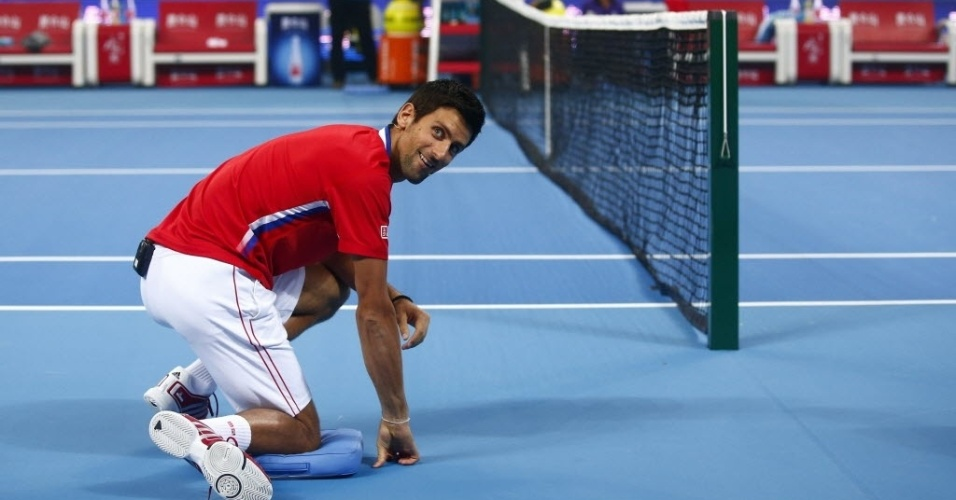 27.set.2013 - Djokovic faz graça e imita pegador de bola durante amistoso na China