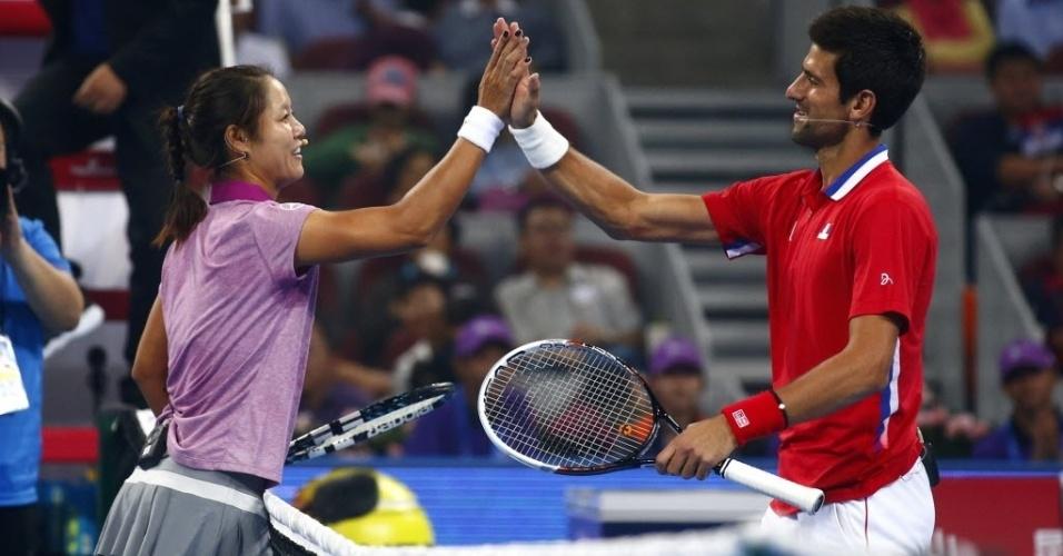 27.set.2013 - Na Li e Novak Djokovic se cumprimentam após partida-exibição em Xangai, para promover os Masters 1000 local