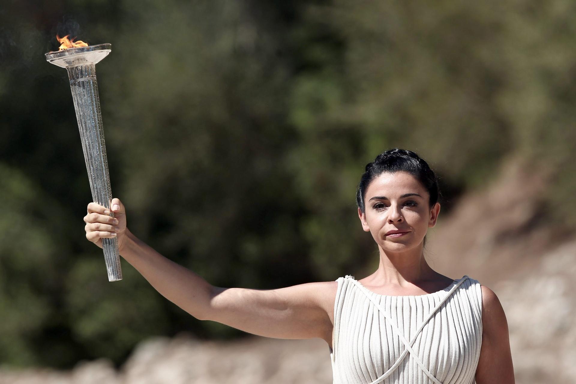 29.set.2013 - A atriz grega, Ino Menegaki, segura a chama olímpica durante a cerimônia ocorrida na Grécia.