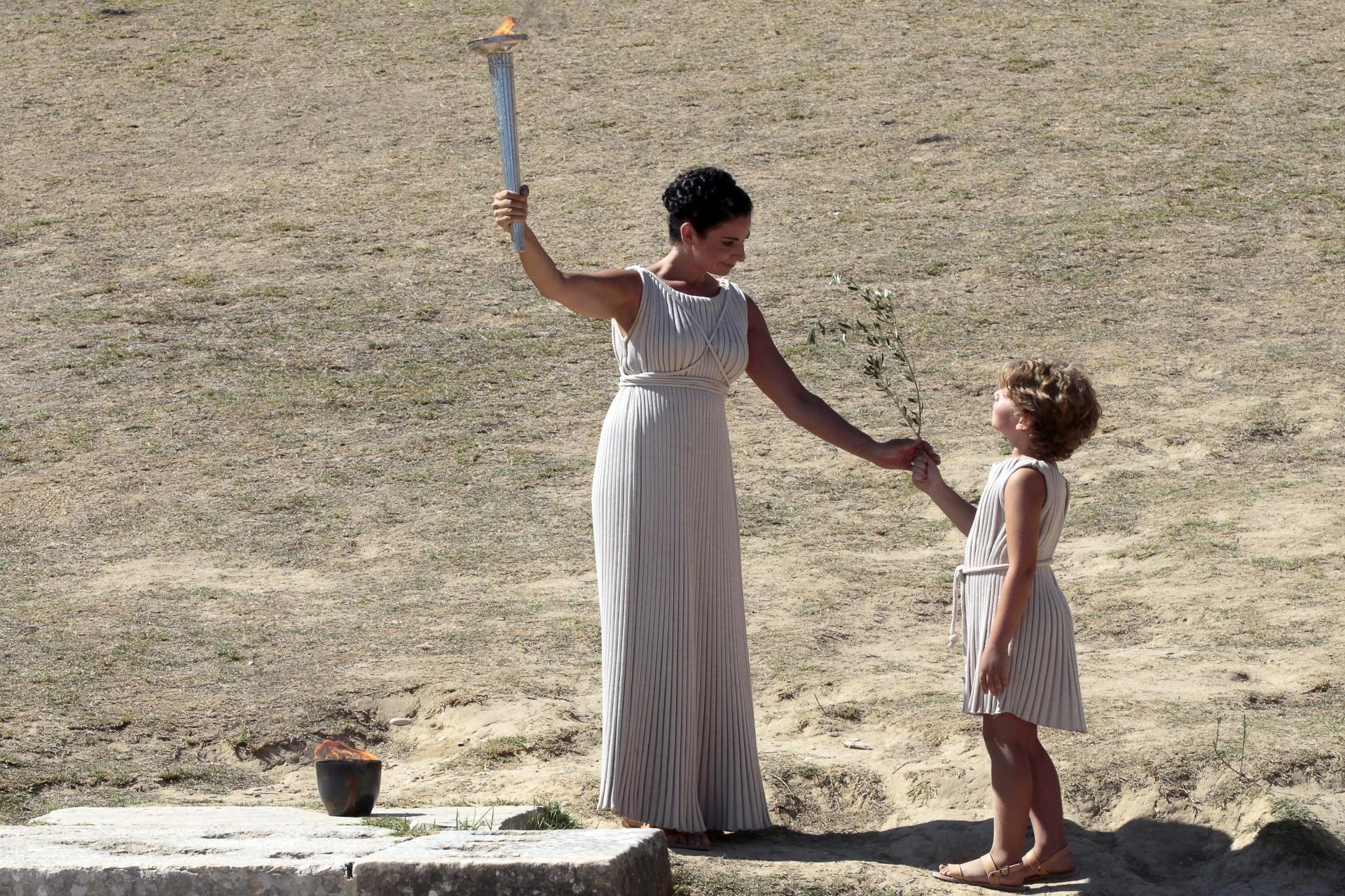 29.set.2013 - Garoto entrega um ramo de oliveira para a sacerdotisa durante a cerimônia da chama olímpica