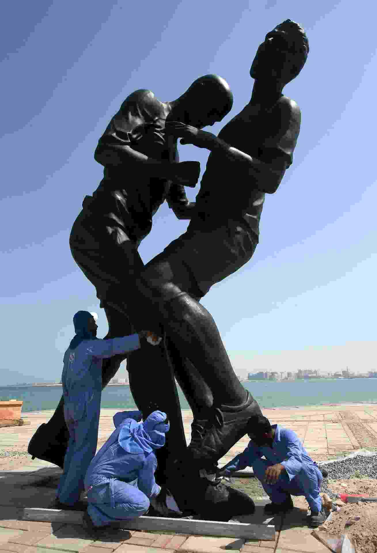 04.10.2013 - Trabalhadores instalam a estátua de Zidane cabeceando o peito de Materazzi em Doha, no Qatar - Karim Jaafar/Al-Watan Doha/AFP Photo