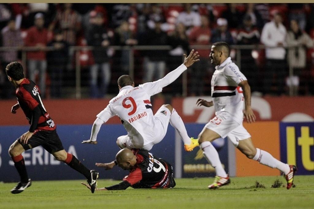 05.out.2013 - Luis Fabiano, do São Paulo, sofre queda após se chocar com o zagueiro Kadu, do Vitória