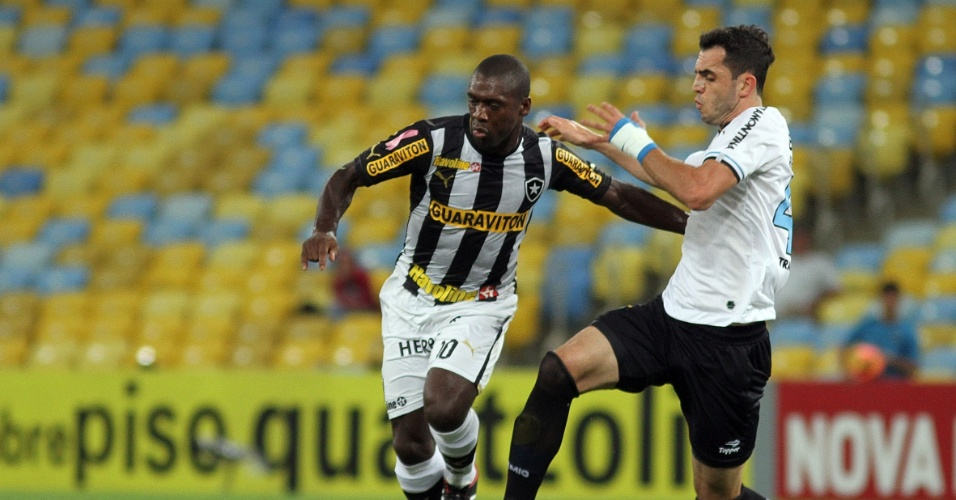 05.out.2013 - Zagueiro Rodolpho, do Grêmio, tenta tirar a bola de Seedorf, do Botafogo