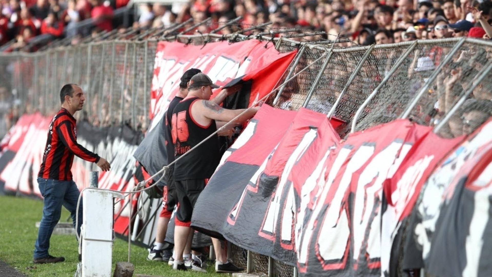 06.out.2013 - Torcedores ajudam a segurar alambrado que entortou após confusão na Vila Capanema, no intervalo do Atletiba