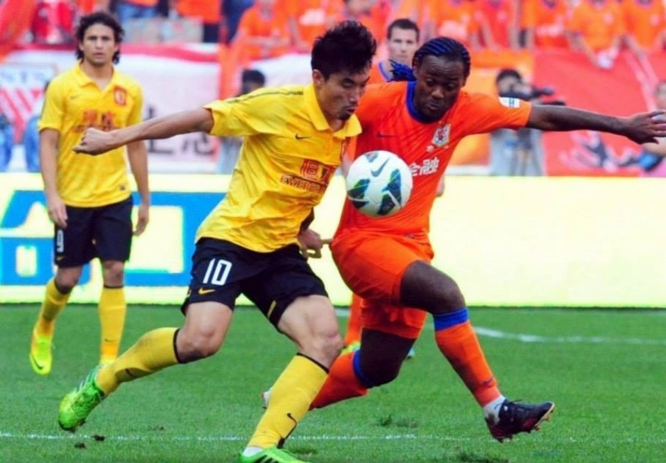 06.out.2013 - Vágner Love, do Shandong Luneng, disputa a bola com jogador do Guangzhou Evergrande, tricampeão chinês