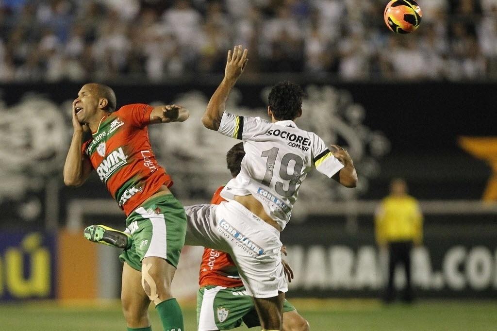 06.out.2013 - Valdomiro, da Portuguesa, coloca a mão no rosto após dividida com William José, do Santos