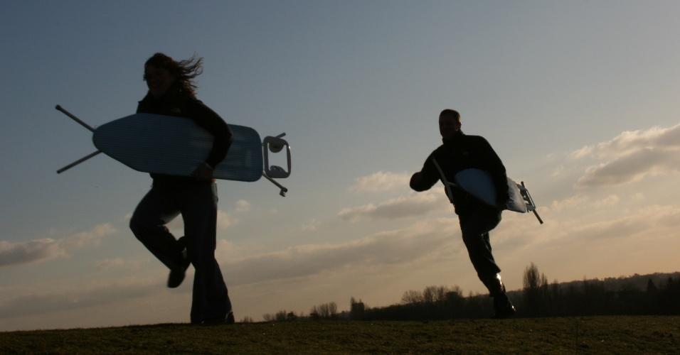 Dois atletas do Steam Team correm com tábuas de passar