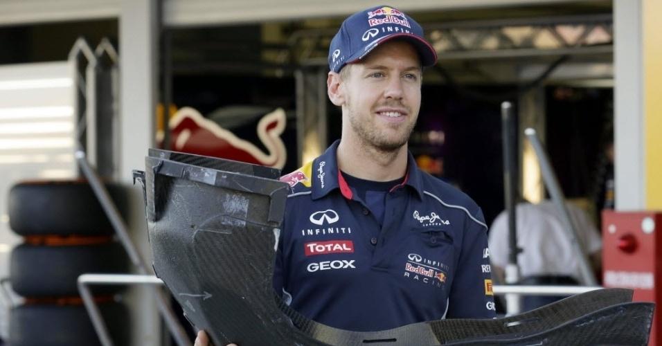 10.out.2013 - Sebastian Vettel carrega perta do banco de seu carro ao chegar ao autódromo de Suzuka, no Japão
