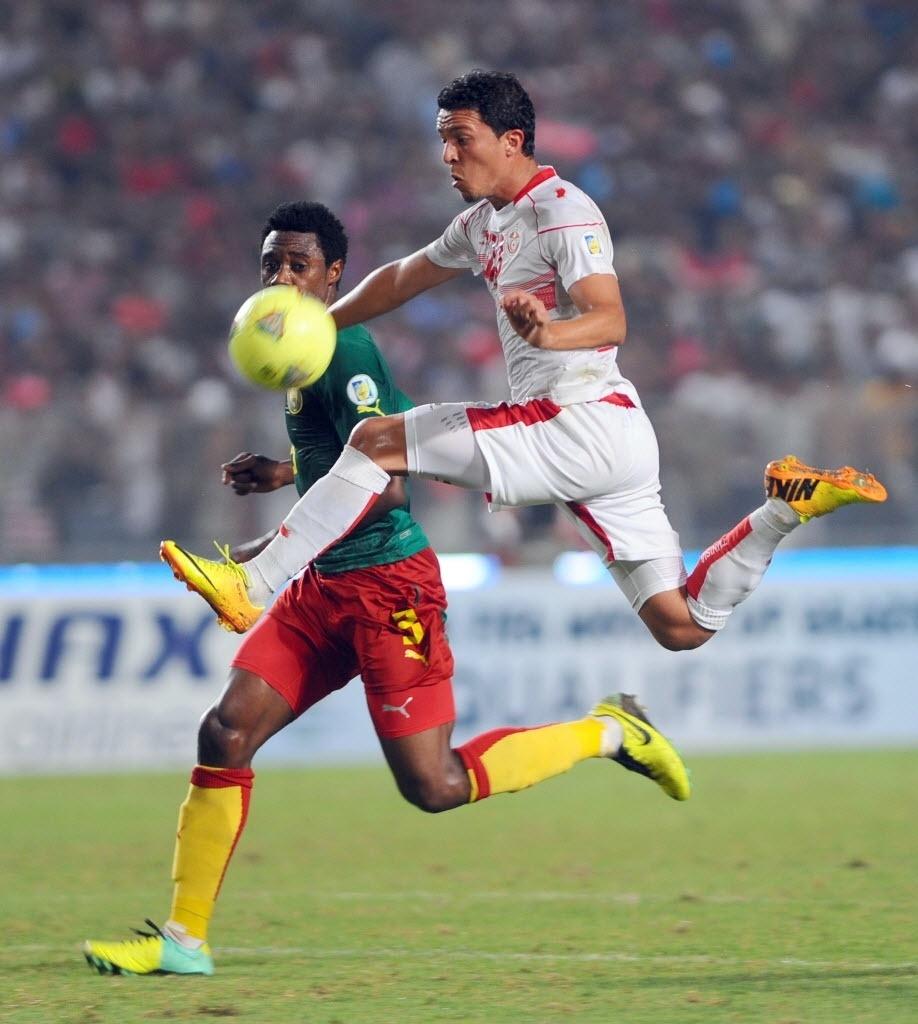 Amine Chermiti, à direita, da Tunísia, é observado por Nkoulou, de Camarões, em duelo pelas eliminatórias da Copa-14; jogo terminou 0 a 0
