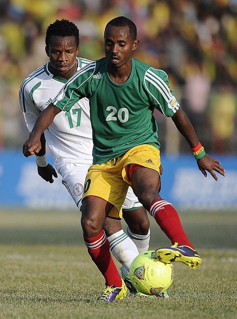 13.out.2013 - Eddy Onazi (nº 17), da Nigéria, fica para trás na disputa de bola com Behailu Assefa, da Etiópia, em partida pelas eliminatórias da Copa-2014; nigerianos venceram por 2 a 1