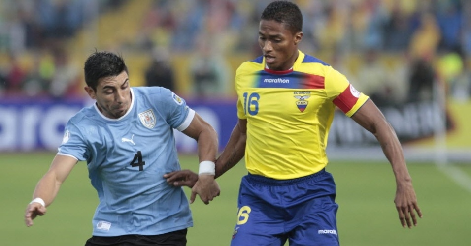 11.out.2013 - Antonio Valencia (d), do Equador, disputa jogada com Jorge Fucile, do Uruguai, em jogo das eliminatórias da Copa-2014; euqatorianos venceram por 1 a 0