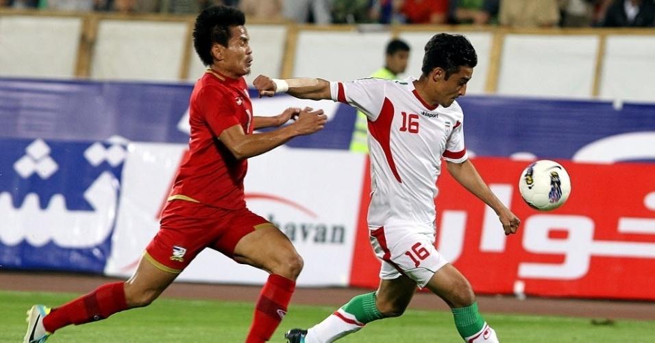15.out.2013 - Chonlatit Jantakam, da Tailândia, persegue Reza Ghoochannejhad, do Irão, para tentar desarmá-lo em jogo válido pelas Eliminatórias Asiáticas