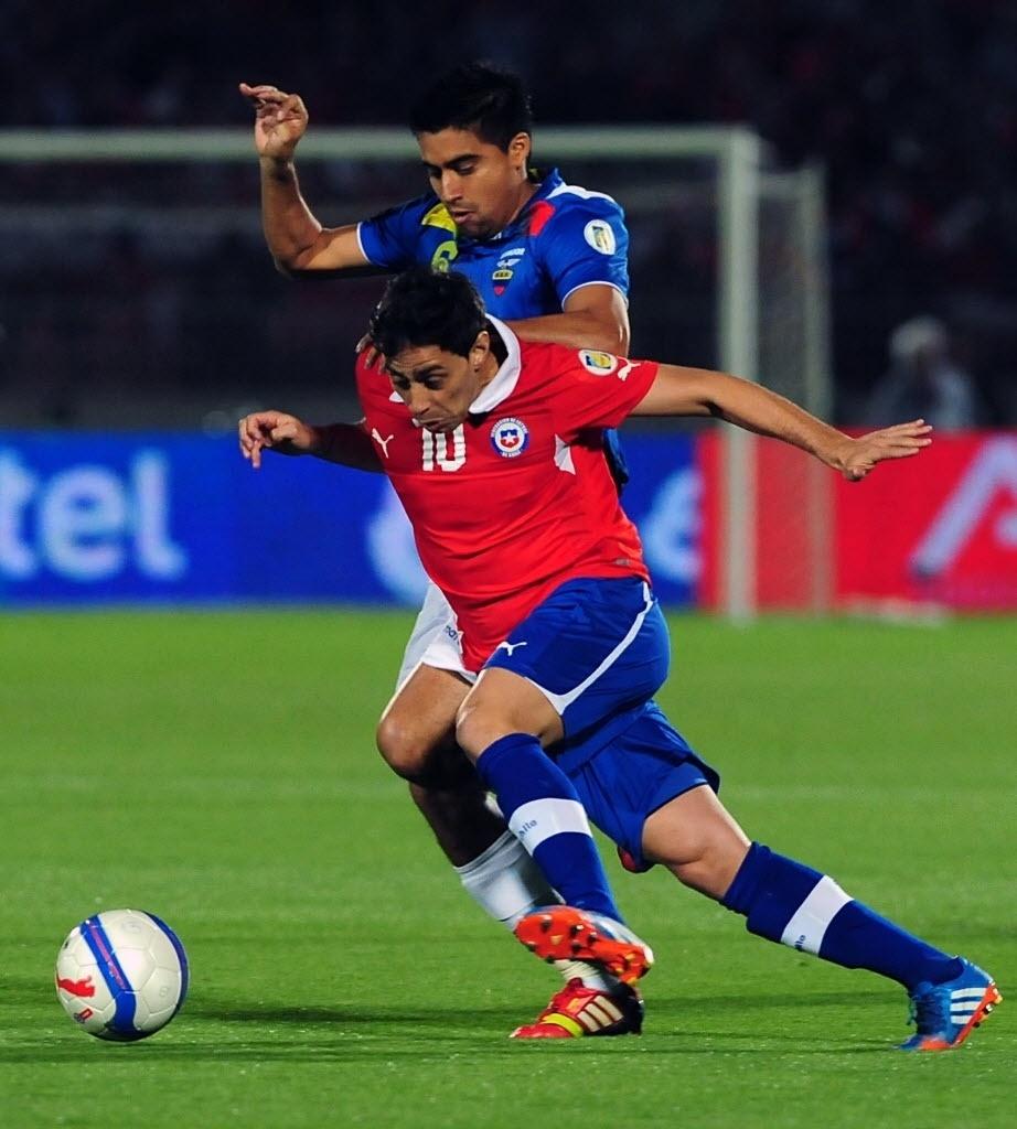 15.out.2013 - Jorge Valdivia, meia do Palmeiras e da seleção do Chile, controla a bola diante da marcação de Christian Noboa, do Equador, em partida das eliminatórias da Copa-2014