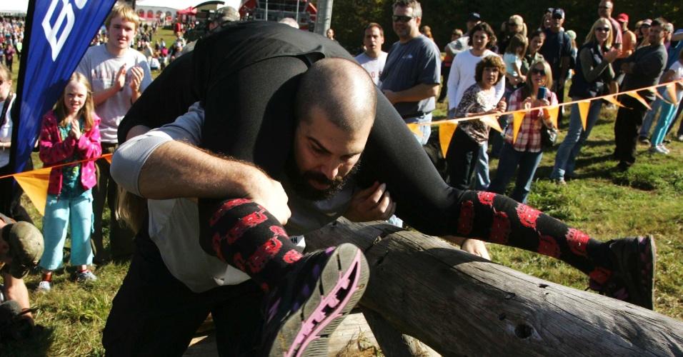 Casal passa pela trave de madeira, um dos obstáculos terrestres da prova
