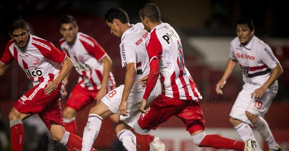 16.out.2013 - Paulo Henrique Ganso é cercado por jogadores do Náutico na jogada do segundo gol do São Paulo em jogo pelo Brasileiro