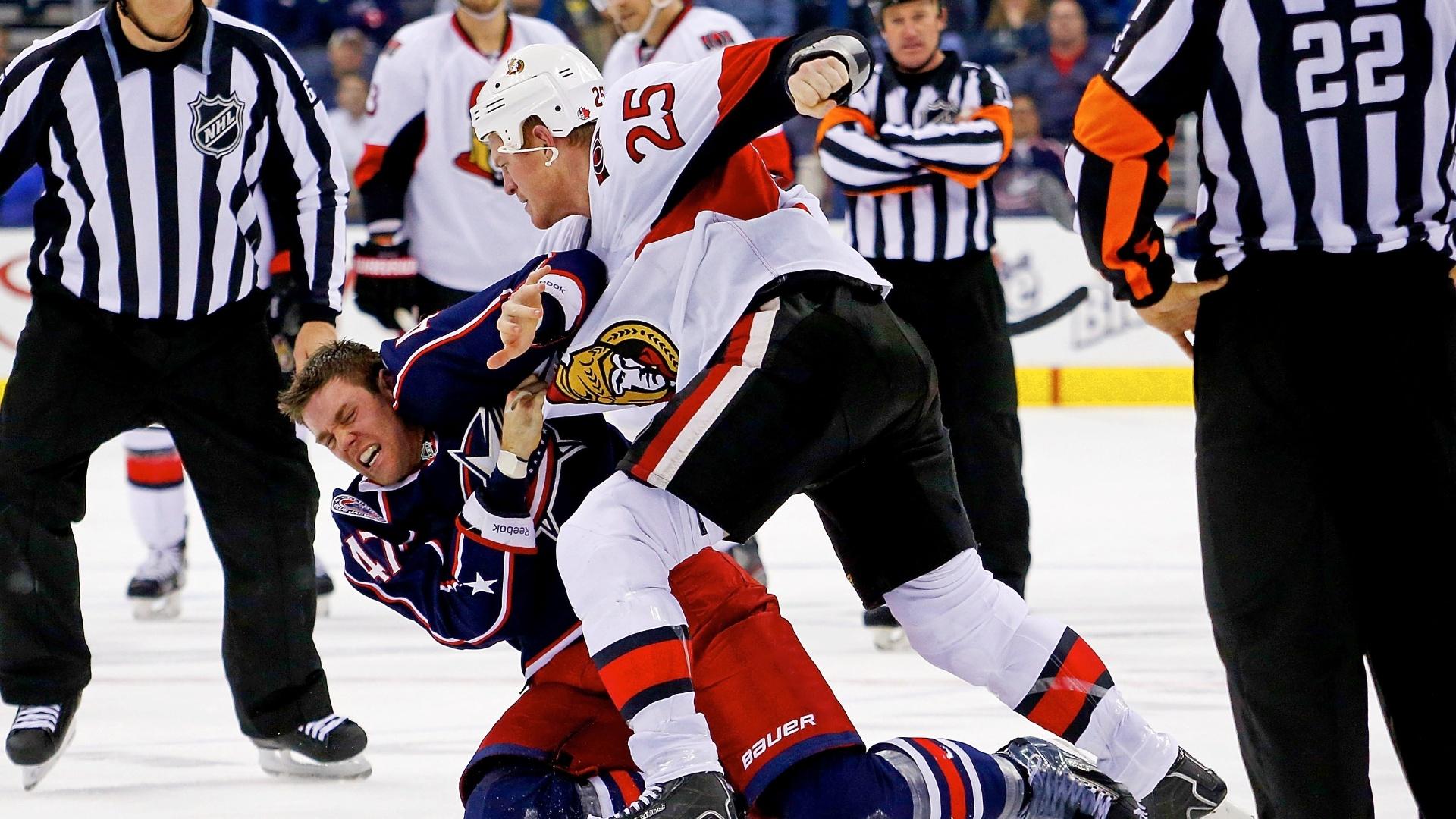 5.Nov.2013 - Chris Neil, do Ottawa Senators, tenta acertar Dalton Prout, do Columbus Blue Jackets, em jogo da NHL, a liga dos EUA de hóquei. Detalhe para o juiz ao fundo, que espera, de braços cruzados, o fim da briga para reiniciar o jogo