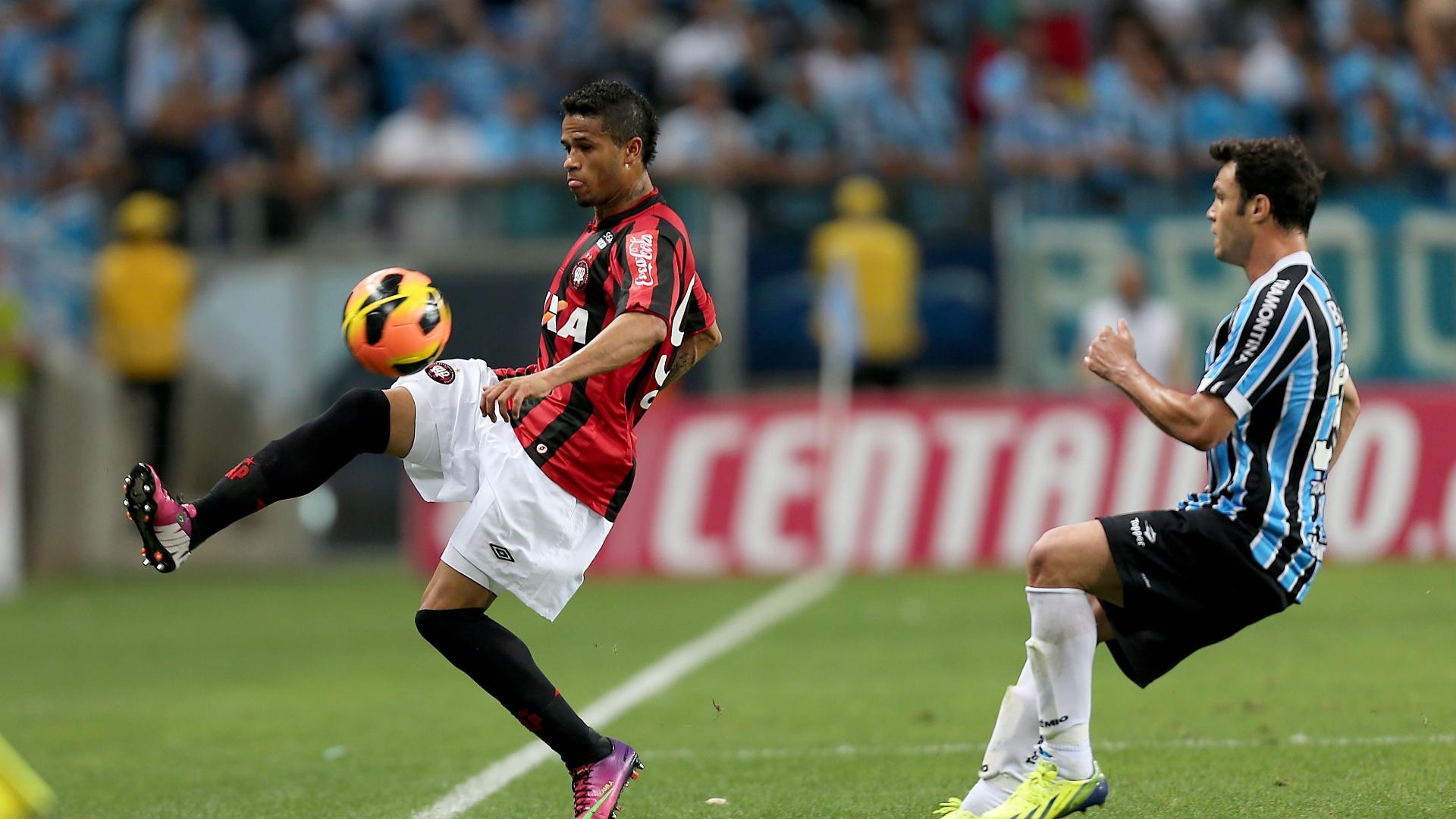 Léo domina a bola enquanto é marcado por Kleber no jogo entre Atlético-PR e Grêmio