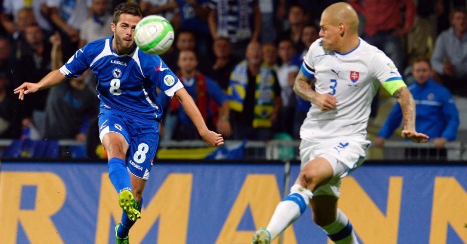 10.set.2013 - Observado por Martin Skrtl, da Eslováquia, Miralem Pjanic, da Bósnia, tenta dominar a bola durante partida pelas eliminatórias da Copa do Mundo-2014