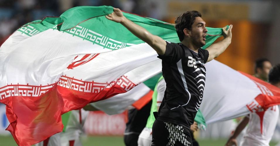 18.jun.2013 - Com a bandeira do Irã, Alireza Haghighi comemora a classificação do país para a Copa do Mundo-2014 com a vitória por 1 a 0 sobre a Coreia do Sul