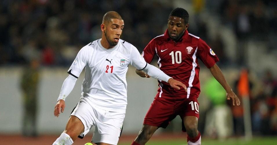 29.fev.2012 - Ashkan Dejagah (e), do Irã, disputa jogada com Khalfan Ibrahim, do Qatar, em partida pelas eliminatórias da Copa do Mundo-2014
