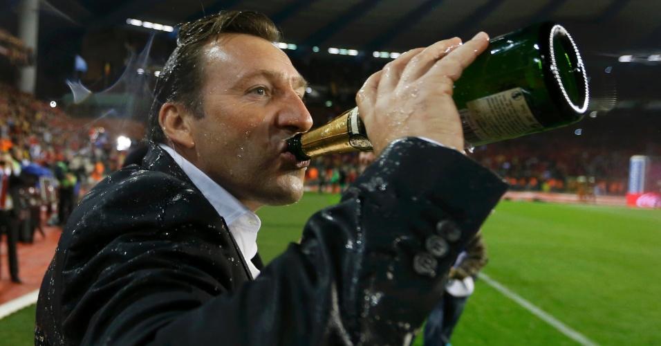 15.out.2013 - Marc Wilmots, técnico da Bélgica, bebe champanhe após o empate por 1 a 1 com País de Gales; equipe já havia se classificado de forma antecipada para a Copa-2014 após vencer a Croácia