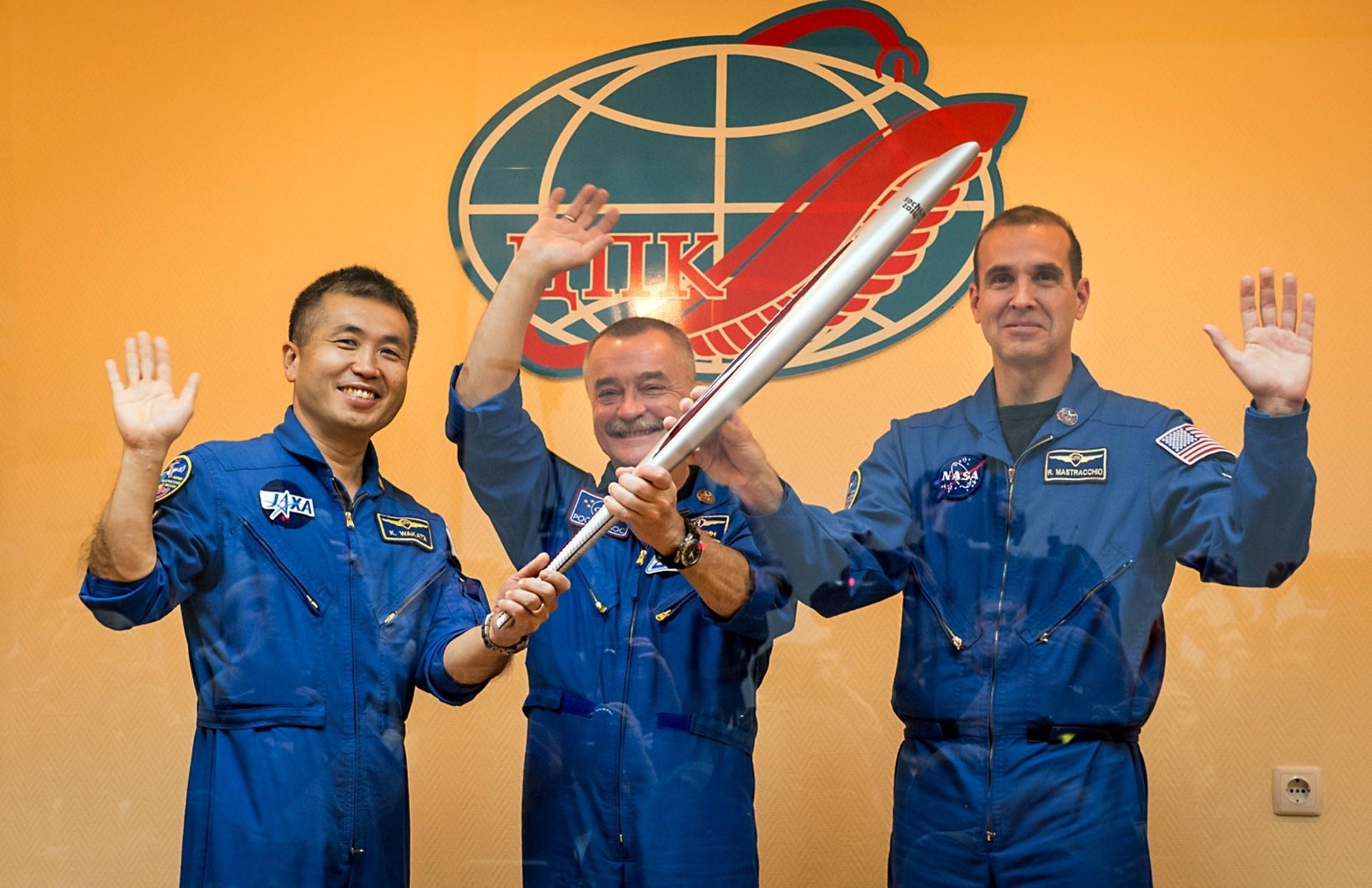 Astronautas posam com a tocha olímpica antes de embarcar no foguete rumo ao espaço