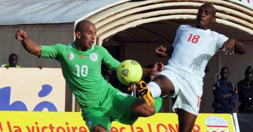 12.out.2013 - Sofiane Feghouli (e), da Argélia, disputa a bola com Charles Kaboré, de Burkina Faso, em partida pelas eliminatórias da Copa-2014; Burkina Fasso venceu por 3 a 2