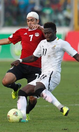 15.out.2013 - Sulley Muntari (d), de Gana, disputa jogada com Ahmed Fathy, do Egito, durante partida das eliminatórias da Copa-2014; ganenses golearam por 6 a 1