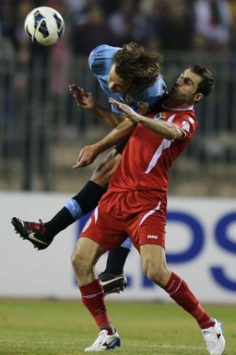 13.nov.2013 - Diego Lugano supera Ahmad Hayel na disputa entre Uruguai e Jordânia; uruguaios golearam por 5 a 0 na partida de ida da repescagem mundial para a Copa-2014