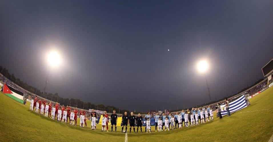 13.nov.2013 - Jogadores de Jordânia e Uruguai ficam perfilados para a execução dos hinos nacionais antes do jogo de ida da repescagem mundial para a Copa-2014