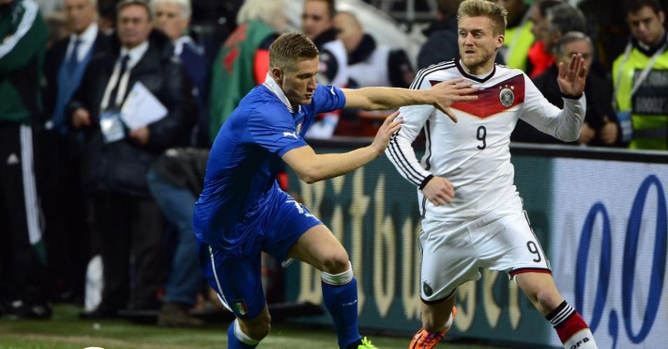 15.nov.2013 - Andre Schürrle (d), da Alemanha, tenta passar pela marcação de Ignazio Abate, da Itália; partida amistosa terminou empatada por 1 a 1