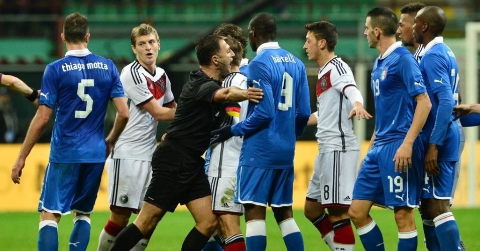 15.nov.2013 - Árbitro tenta separar jogadores de Itália e Alemanha após confusão no amistoso. Confronto terminou empatado por 1 a 1