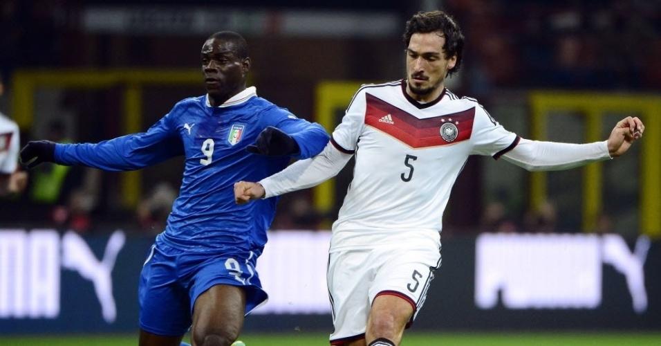 15.nov.2013 - Mario Balotelli, da Itália, divide a bola com Mats Hummels, da Alemanha, no amistoso em San Siro; partida terminou empatada por 1 a 1