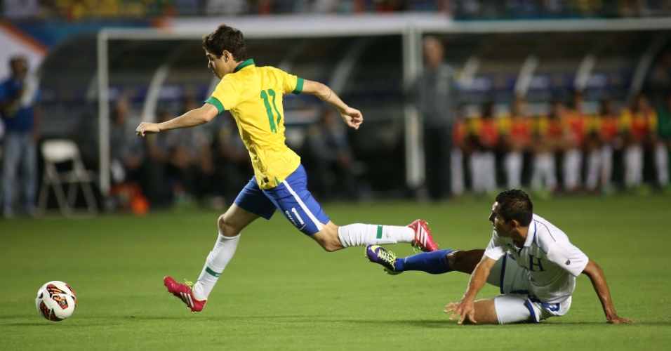 16.nov.2013 - Hondurenho fica no chão, e Oscar parte com a bola dominada durante amistoso da seleção brasileira em Miami
