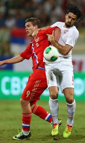 15.nov.2013 - Alexander Kokorin (e), da Rússia, briga pela bola com Milan Bisevac, da Sérvia, durante amistoso disputado em Dubai; jogo terminou 1 a 1