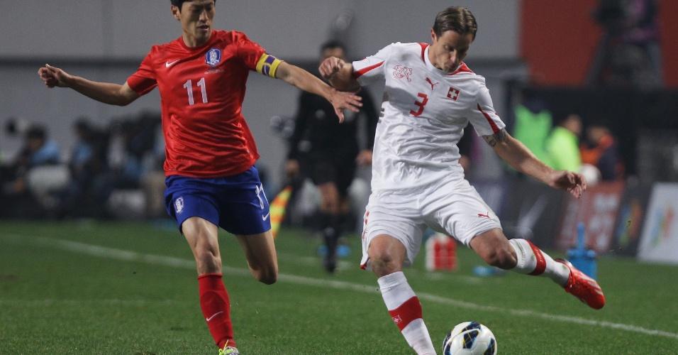 15.nov.2013 - Marcado por Lee Chung-Yong, da Coreia do Sul, Reto Ziegler, da Suíça, tenta tocar a bola durante amistoso disputado em Seul; sul-coreanos ganharam por 2 a 1