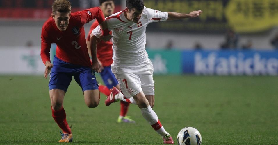 15.nov.2013 - Tranquillo Barnetta (d), da Suíça, disputa jogada com Lee Yong , da Coreia do Sul, durante amistoso disputado em Seul; sul-coreanos venceram por 2 a 1