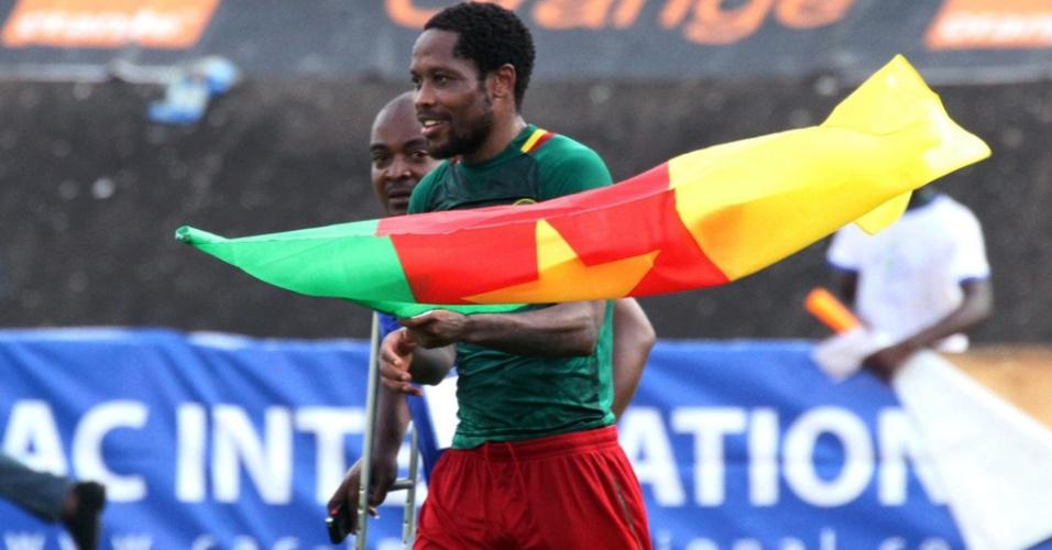 17.nov.2013 - Com a bandeira de Camarões, Jean Makoun comemora a classificação dos Leões Indomáveis para a Copa-2014 após a goleada por 4 a 1 sobre a Tunísia