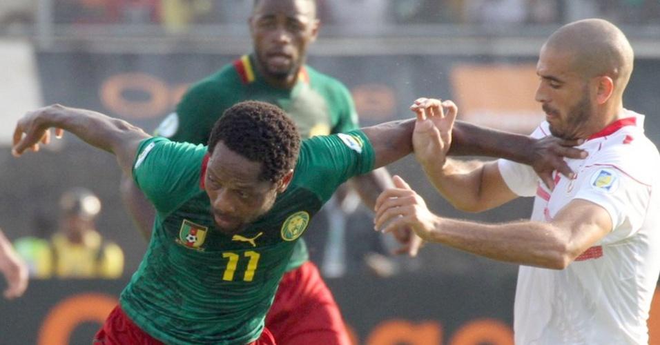 17.nov.2013 - Jean Makoun (e), de Camarões, tenta se livrar da forte marcação de Regued Houcine, da Tunísia; camaroneses venceram por 4 a 1 e se classificaram para a Copa-2014