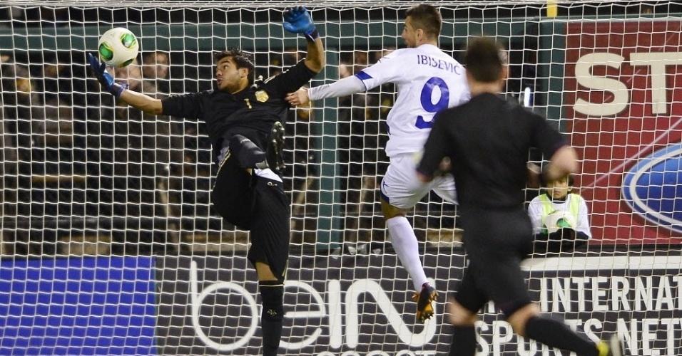 18.nov.2013 - Romero salva lance para a Argentina em dividida com Ibisevic, da Bósnia; argentinos venceram amistoso por 2 a 0