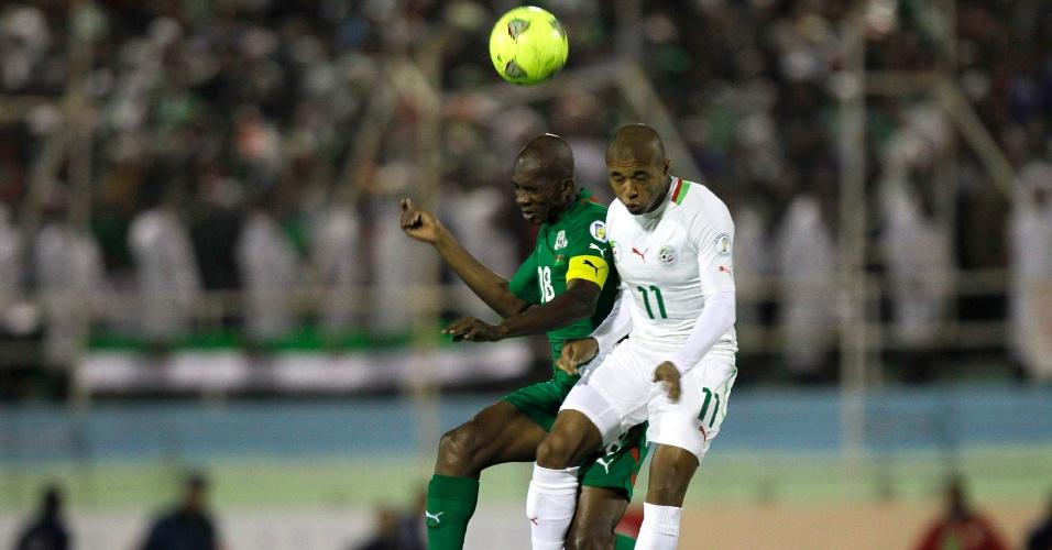 19.nov.2013 - Charles Kaboré (e), de Burkina Fasso, disputa jogada pelo alto com Yacine Brahimi, da Argélia; argelinos venceram por 1 a 0 e se classificaram para a Copa do Mundo-2014