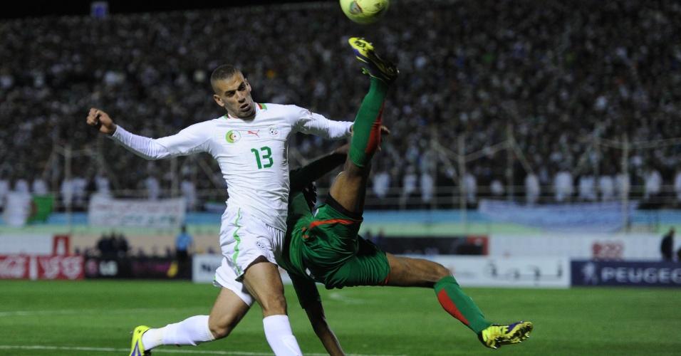 19.nov.2013 - Islam Slimani (e), da Argélia, disputa jogada com Benjamin Balima, de Burkina Fasso; argelinos ganharam por 1 a 0 e se classificaram para a Copa do Mundo-2014