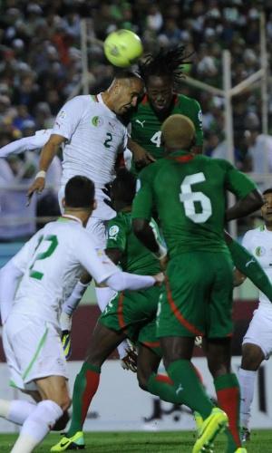 19.nov.2013 - Madjid Bougerra (e), da Argélia, disputa jogada pelo alto com Bakary Koné, de Burkina Fasso; argelinos venceram por 1 a 0 e se classificaram para a Copa-2014
