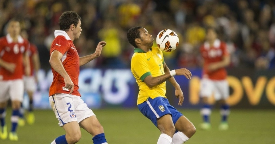 19.nov.2013 - Robinho é vigiado de perto pelo chileno Mena em amistoso da seleção em Toronto (Canadá); Brasil venceu por 2 a 1