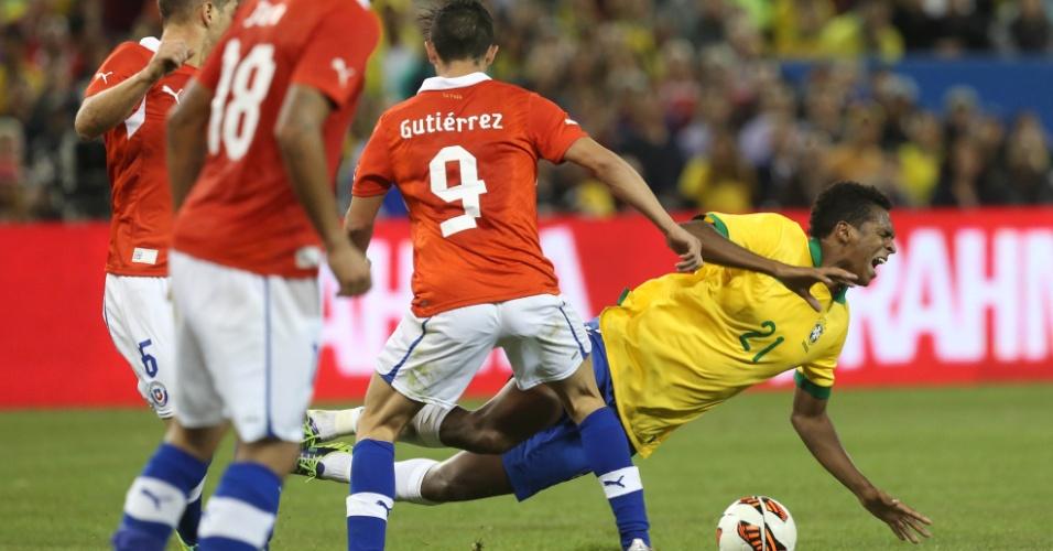 19.nov.2013 - Jô, da seleção brasileira, é derrubado pelo chileno Gutiérrez durante amistoso em Toronto; brasileiros venceram por 2 a 1